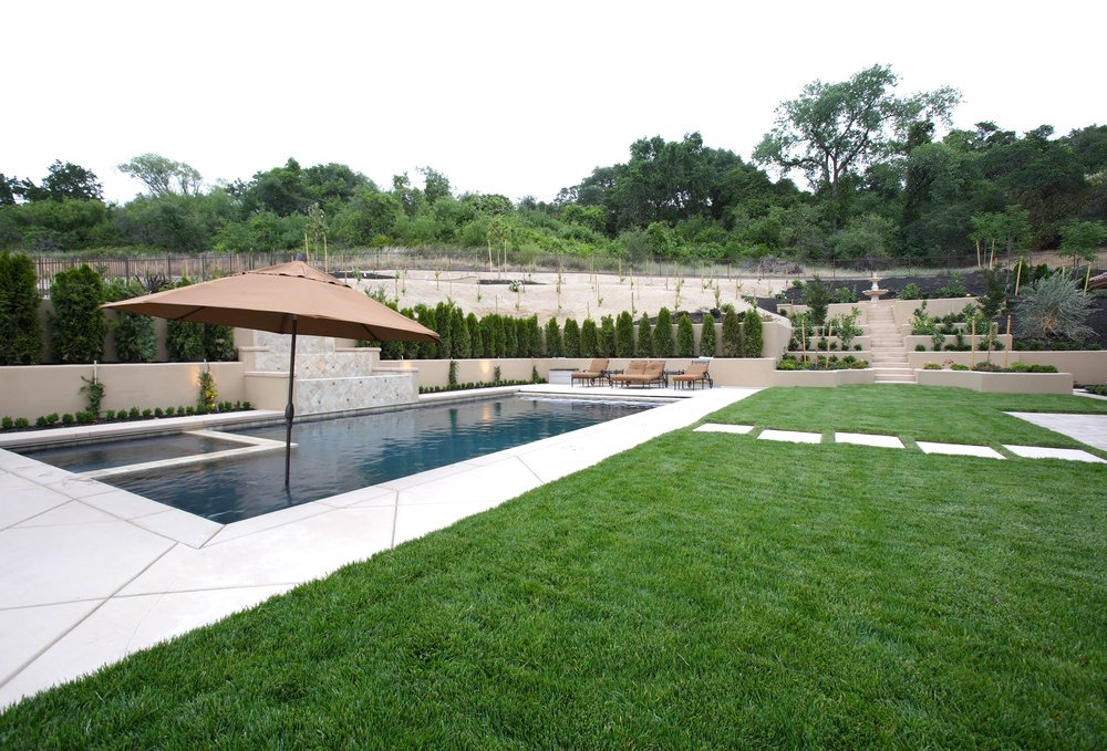 An in-ground pool lined with pine trees and plants showcasing a marbled water feature in the middle. There's a concrete staircase at the far end with layered planters on the sides leading to a lovely fountain.
