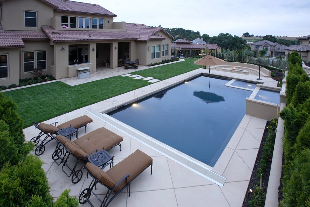 A beige house with a concrete pathway leading to the rectangular swimming pool with a hot tub. It sits in between metal mobile loungers fitted with tufted brown cushions and fire pit with built-in seating.