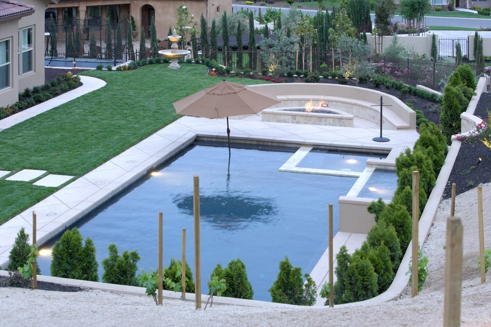 This house features a fountain on the green lush lawn and a swimming pool with a fire pit and a curved built-in seating on its edge.