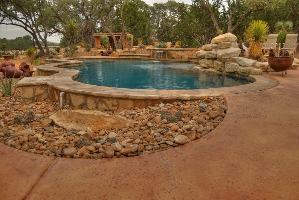 A stone swimming pool with a water feature surrounded by desert plants and trees. It offers a fire pit next to the boulders which are another highlight of this pool.