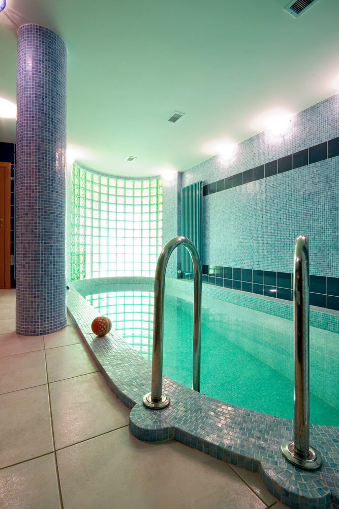 Serene indoor pool lined with a column clad in blue mosaic tiles that match with the wall. It is illuminated by sconces and natural light that streams through the frosted glass block window.