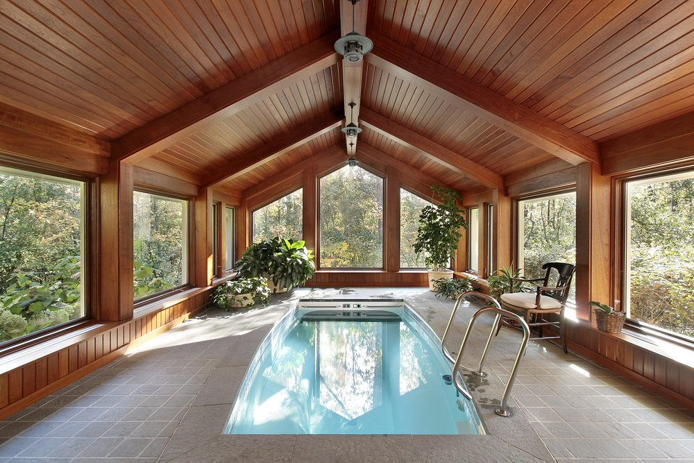 A modern swimming pool inside this room surrounded with glass paneled windows that overlook the majestic forest. It has concrete flooring and vaulted ceiling with wood beams and hanging semi-flush mount lights.