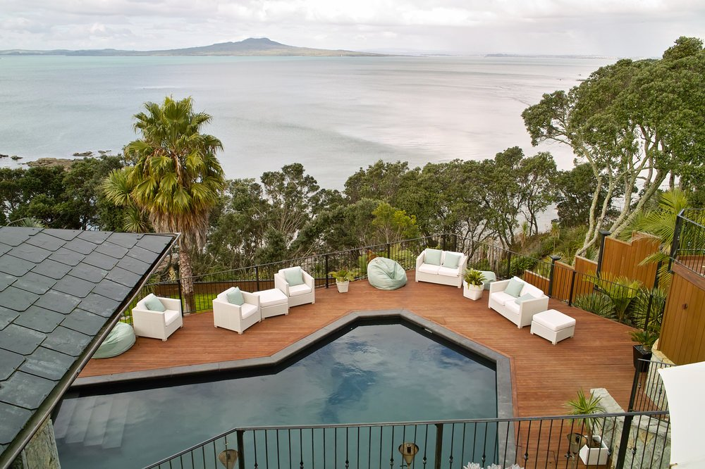 A house with a spectacular ocean view showcases a swimming pool surrounded with wooden deck and white comfy seats that are topped with mint green pillows matching with the bean bag chairs.