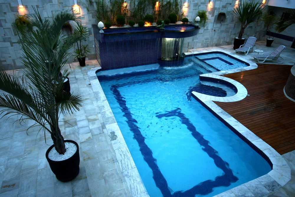 An L-shaped swimming pool boasts a fancy waterfall feature fixed to the stone wall that matches with the flooring.  It includes a hot tub and wooden deck beside the striped loungers.
