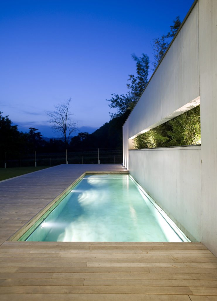 A rectangular swimming pool surrounded with natural wood plank deck and fixed to the white wall with a window that runs the length of the pool.