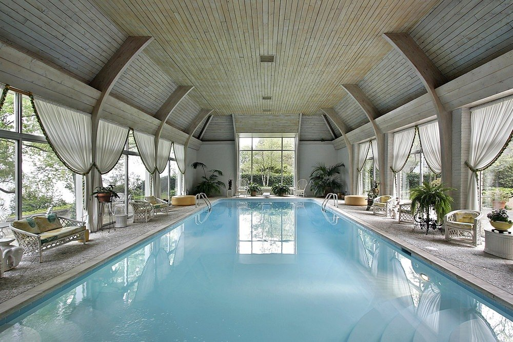 An indoor swimming pool enclosed in wood plank ceiling and full height glazing covered with white sheer curtains. It is furnished with yellow round ottomans and white rattan chairs and benches with floral cushions.