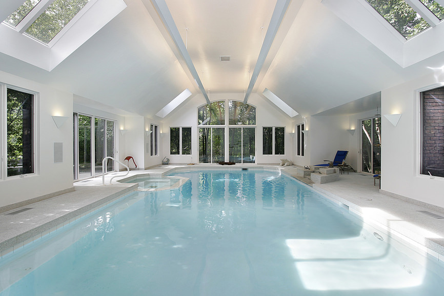 A minimalist indoor pool with a jacuzzi and blue loungers illuminated by wall sconces and skylights fitted on the vaulted ceiling.