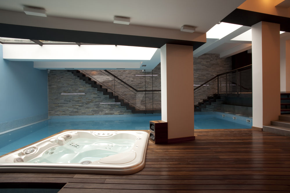 A metal staircase with glass railings leads to this luxury pool accompanied by a modern hot tub spa that's fitted on the wood plank deck.