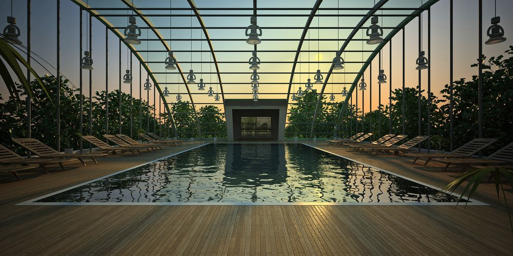 A sleek swimming pool surrounded with teak wood loungers over wood plank deck. It is wrapped in metal framing with hanging lighting fixtures.
