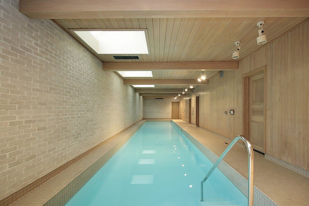 An indoor lap pool surrounded with brick and wood plank walls that extends to the ceiling mounted with track lighting and skylights.