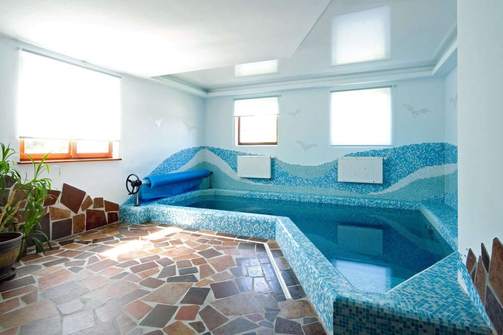 An artsy swimming pool designed with flagstone flooring and waves through multi-colored mosaic tiles that are clad in the white wall.