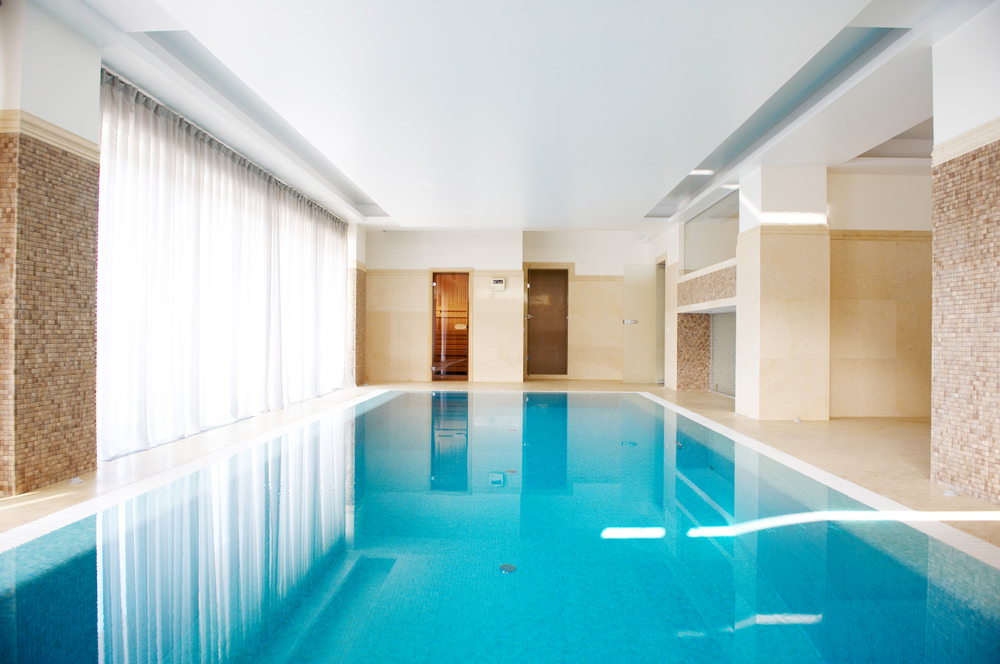 A tranquil swimming pool with marble flooring and floor to ceiling glass windows covered with white sheer curtains.