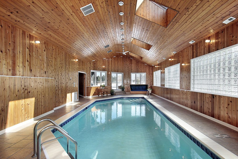 A cozy house enclosed in wood plank walls and ceiling that's fitted with flush mount lights and skylights. It has a pool accompanied by a wooden table and a deep blue cushioned seat.