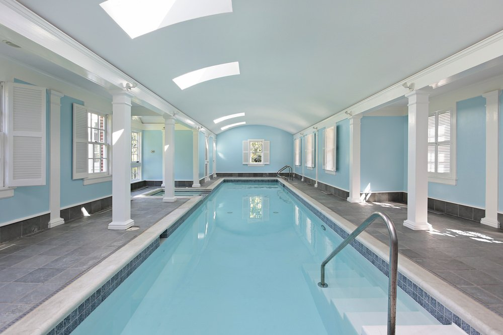 An indoor lap pool lined with white columns and enclosed in light blue walls along with barrel vaulted ceiling that's fitted with skylights.
