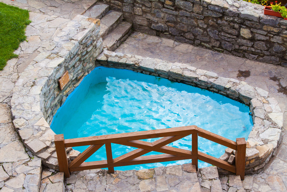 A stone swimming pool surrounded with stone pavers for a unified look. There's a stone stack retaining wall on the side and a staircase framed with a natural wood railing next to the pool.