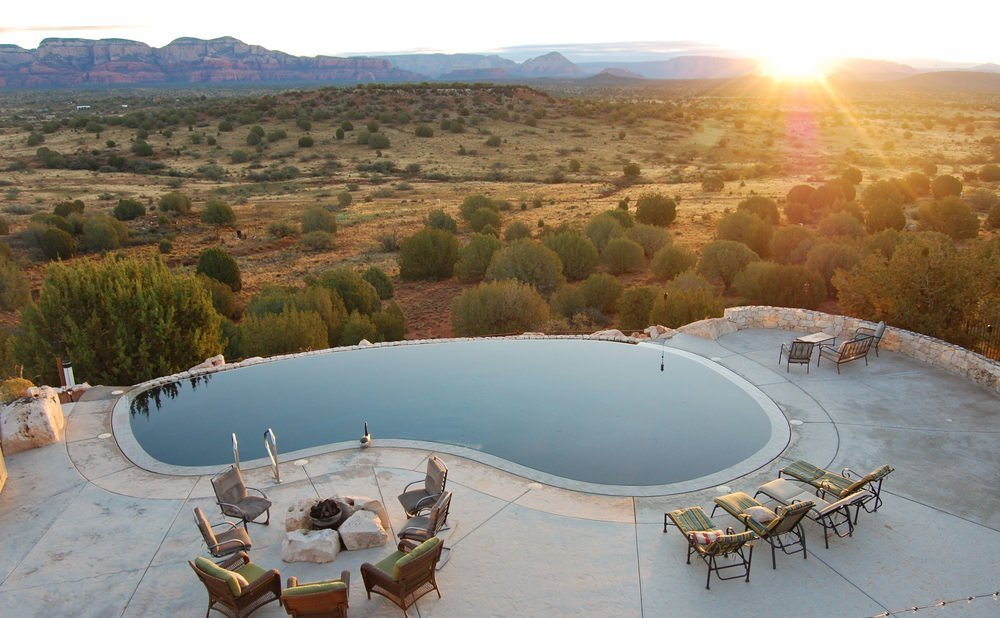 A kidney-shaped pool overlooking an expansive desert view. It offers striped loungers and a fire pit surrounded with gray and green armchairs.
