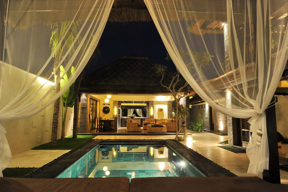 A view of the crystal clear swimming pool from the cabana with comfy seats covered in white sheer curtains. It faces the pool house offering dark wood dining and wicker seating.