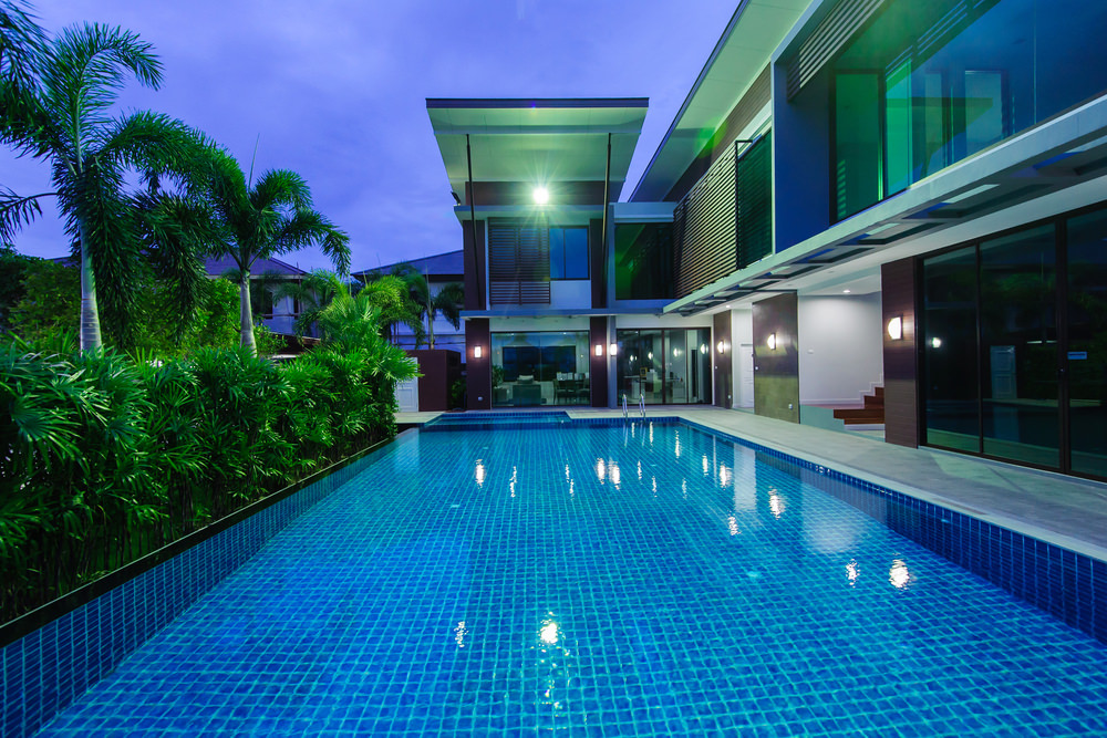 Contemporary house features a swimming pool with crystal clear water and blue mosaic tiles. It is lined with a hedge on the left side that serves as additional privacy to the area.