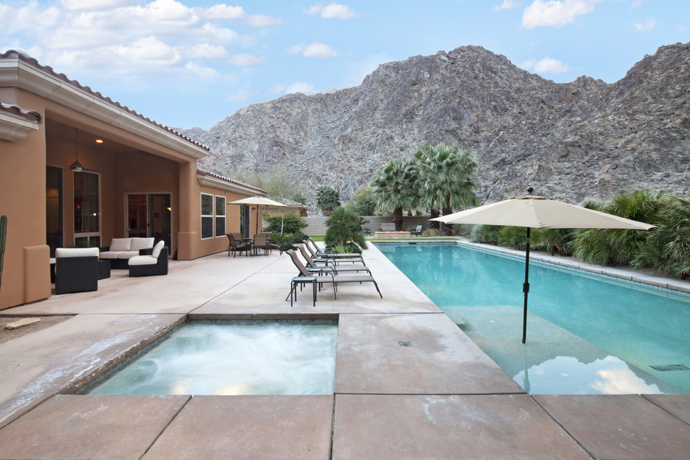 A brown house with a magnificent mountain view offers a lap swimming pool lined with wicker loungers and side tables.