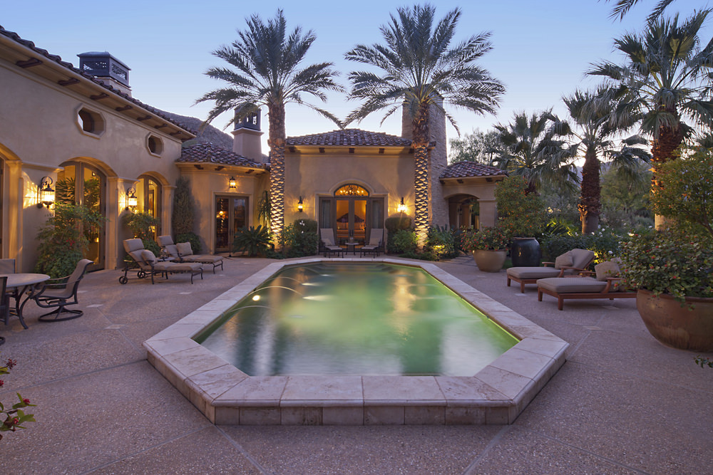 Mediterranean house features a hexagonal swimming pool accompanied with gray lounge chairs over textured pavers.