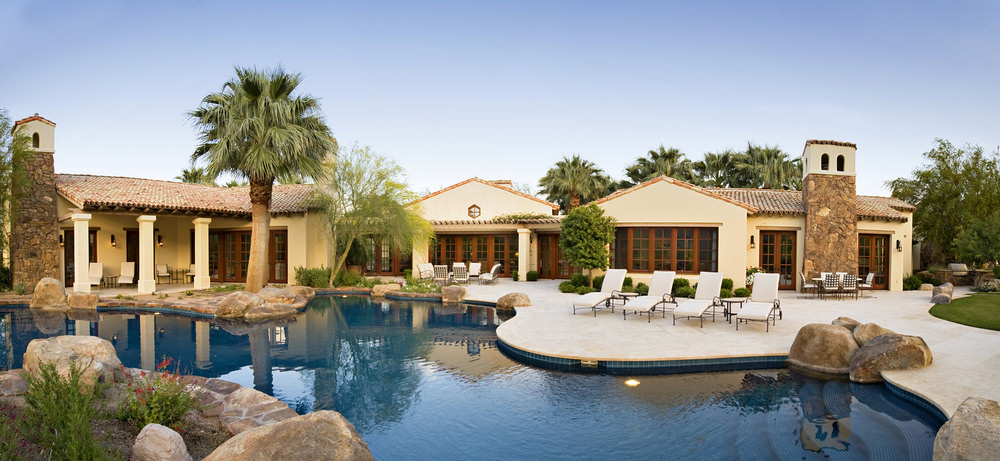 This house showcases an open patio and luxury swimming pool accented with big rocks and white lounge chairs.