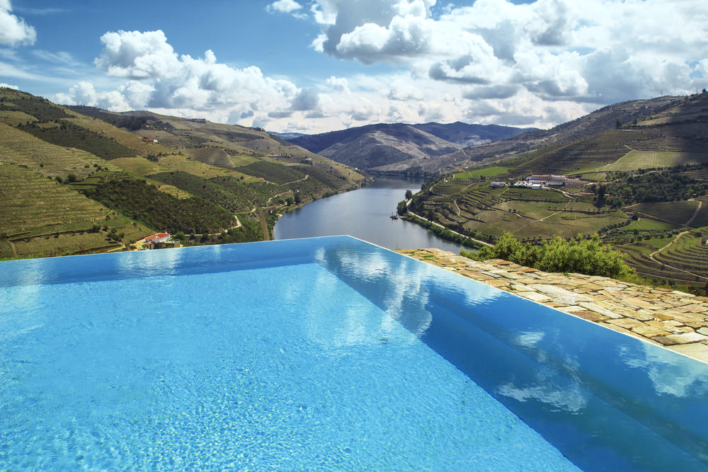 A stunning infinity pool with stone paving overlooking marvelous hill view in between the river.