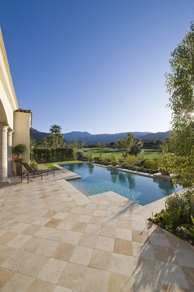 A rattan lounge chair sits beside this swimming pool topped with potted plants and overlooks a spectacular mountain view.