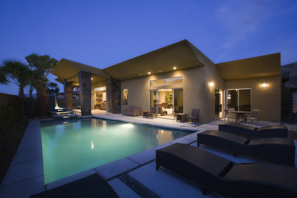 This house offers a tranquil swimming pool with brown lounge chairs over concrete pavers. There are also multiple seating on the side of the house.