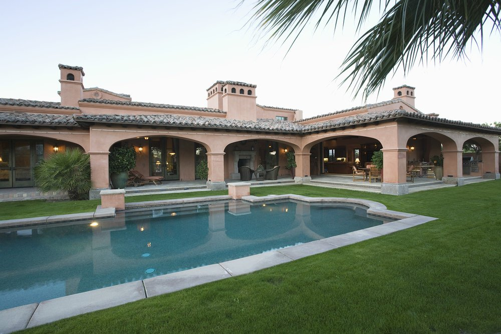 A house that's lined with arches covering the patio offers a rectangular swimming pool surrounded with a lush green lawn.