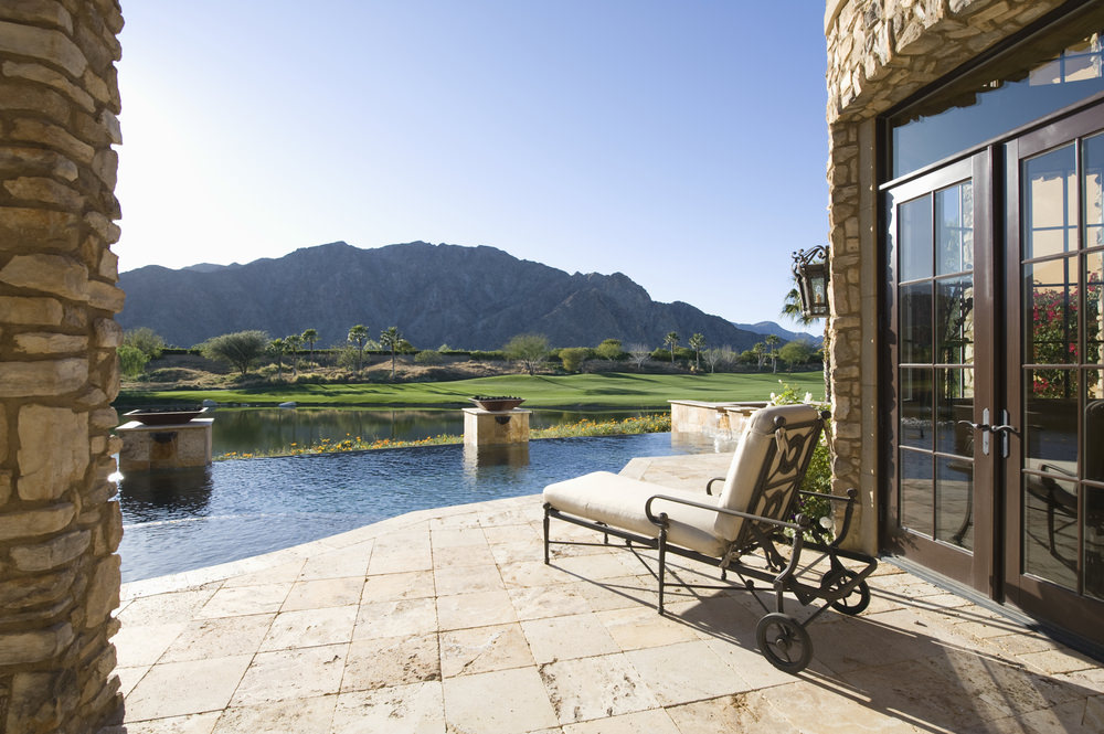 A luxury infinity pool beside the stone house with fire bowls and a mobile lounge chair overlooking a picturesque mountain view.