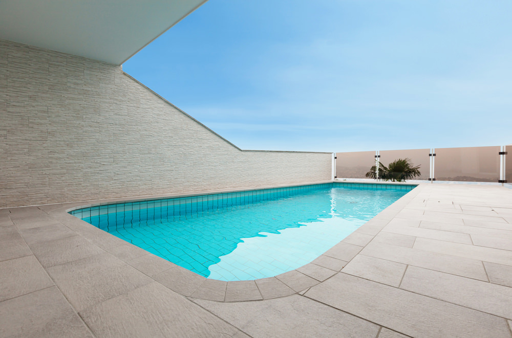 A sleek swimming pool enclosed in tinted glass fence panels and concrete walls that complements with the brick paver for a cohesive look.