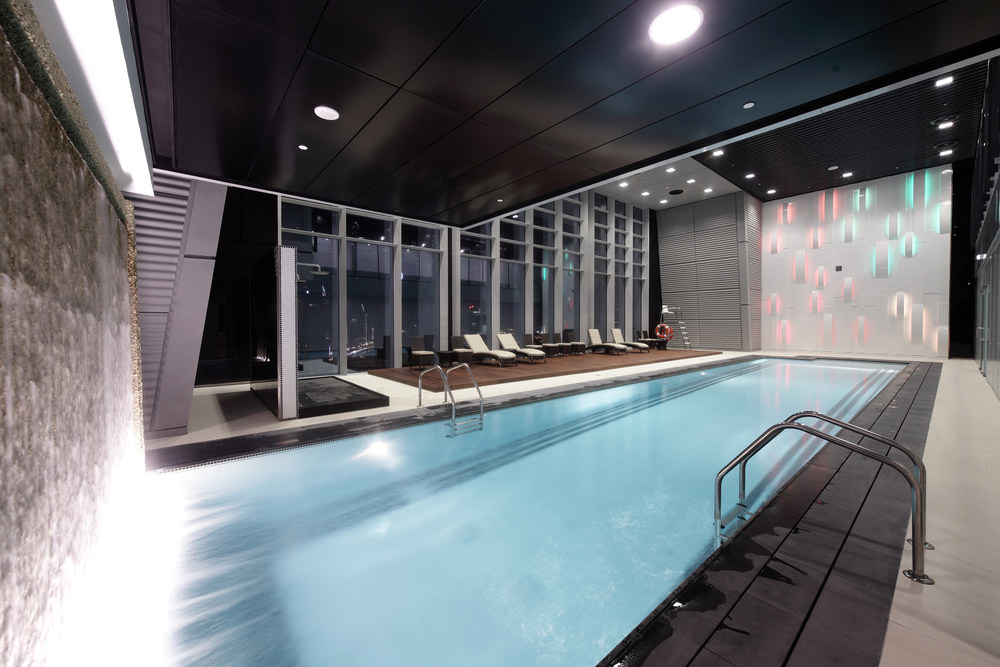 A deluxe swimming pool with beige lounge and cushioned chairs that sit on a wooden platform. It is enclosed with full height glazing and black paneled ceiling that matches with its surround tiles.