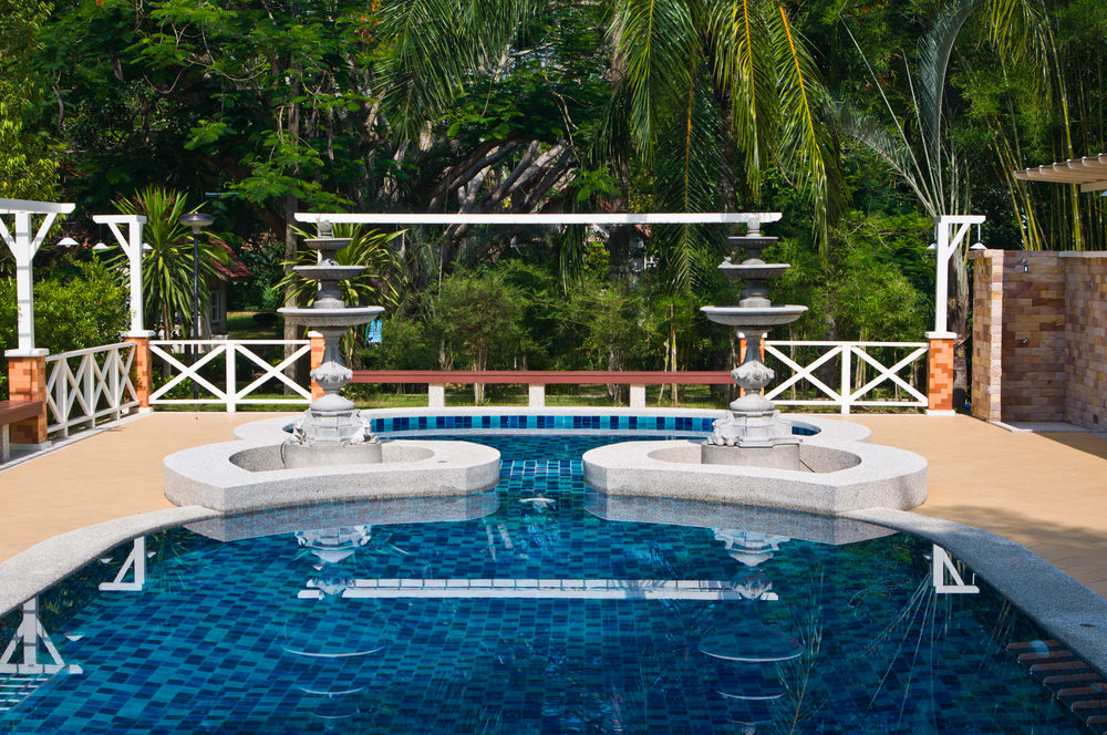 A fabulous swimming pool enclosed in white criss-cross fence features a pair of classic concrete fountains on its edge.