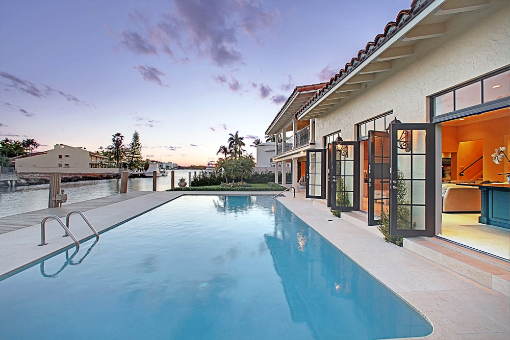 A modern house with glass doors that open to this swimming pool with concrete paver and a wooden boardwalk on the side.