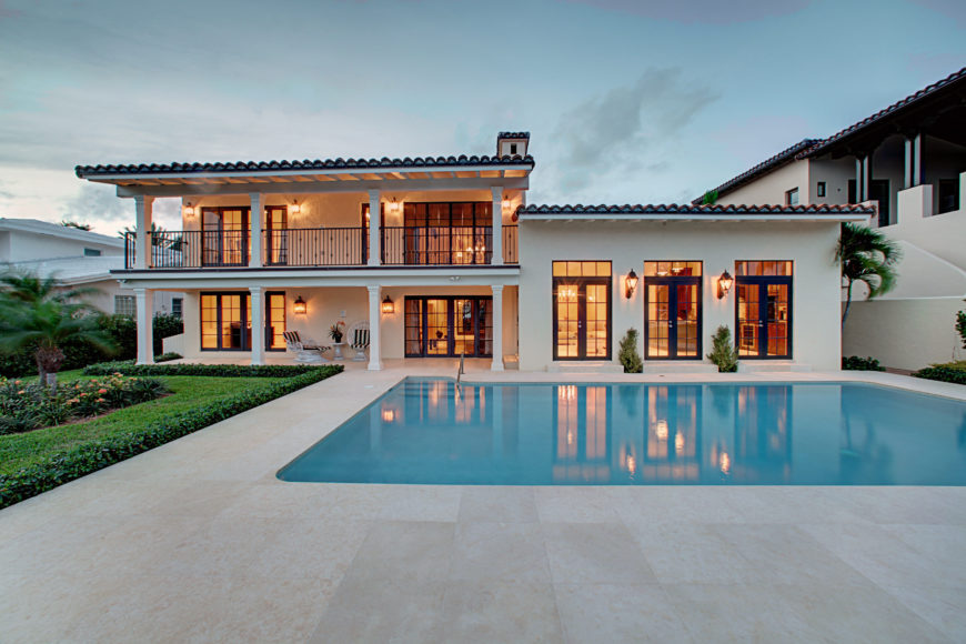 An in-ground swimming pool with lovely landscaping on the side and concrete pavers that complement the modern house lined with columns and framed with wrought iron railing.