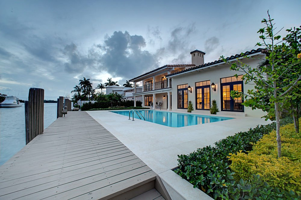 A modern house illuminated by outdoor sconces features a swimming pool with concrete paving and natural wood boardwalk framed with wooden columns.