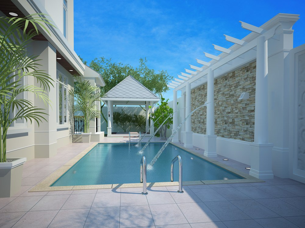 A gorgeous white house features a swimming pool with an empty gazebo and a pergola waterfall feature accented with stone bricks.