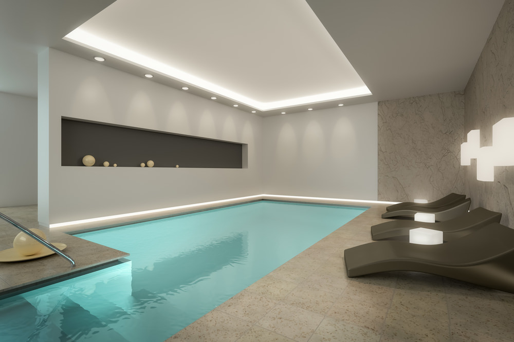 An elegant swimming pool with sleek black lounge chairs and a rectangular inset wall filled with various sized glass globe decors. It is illuminated by wall sconces and recessed lights fitted to the tray ceiling.