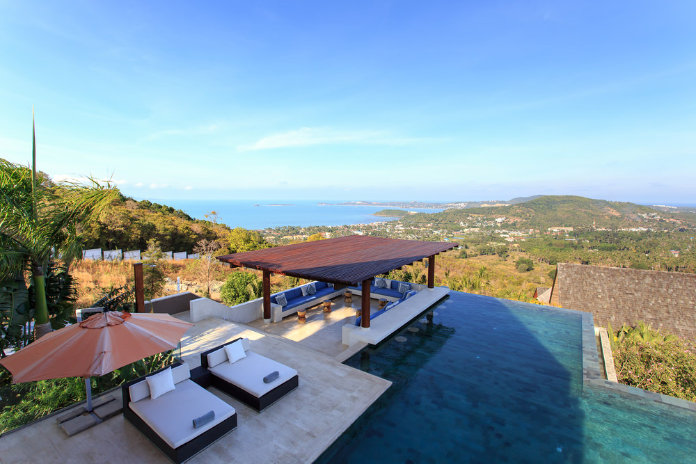 A stunning infinity pool with an expansive view of the mountains and ocean features a pair of comfy lounge beds and a U-shaped seating area topped with blue cushions and patterned pillows.
