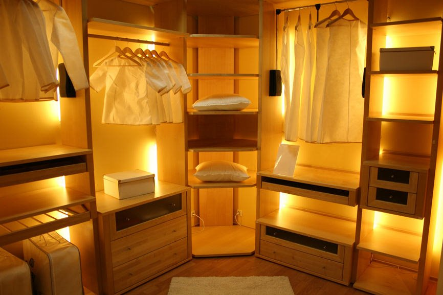 This classy bedroom closet boasts a matching walnut finished flooring and cabinetry with its own dim lights.