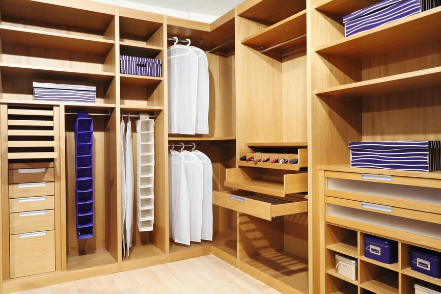 This bedroom closet features a light-finished hardwood flooring along with a walnut finished cabinetry.
