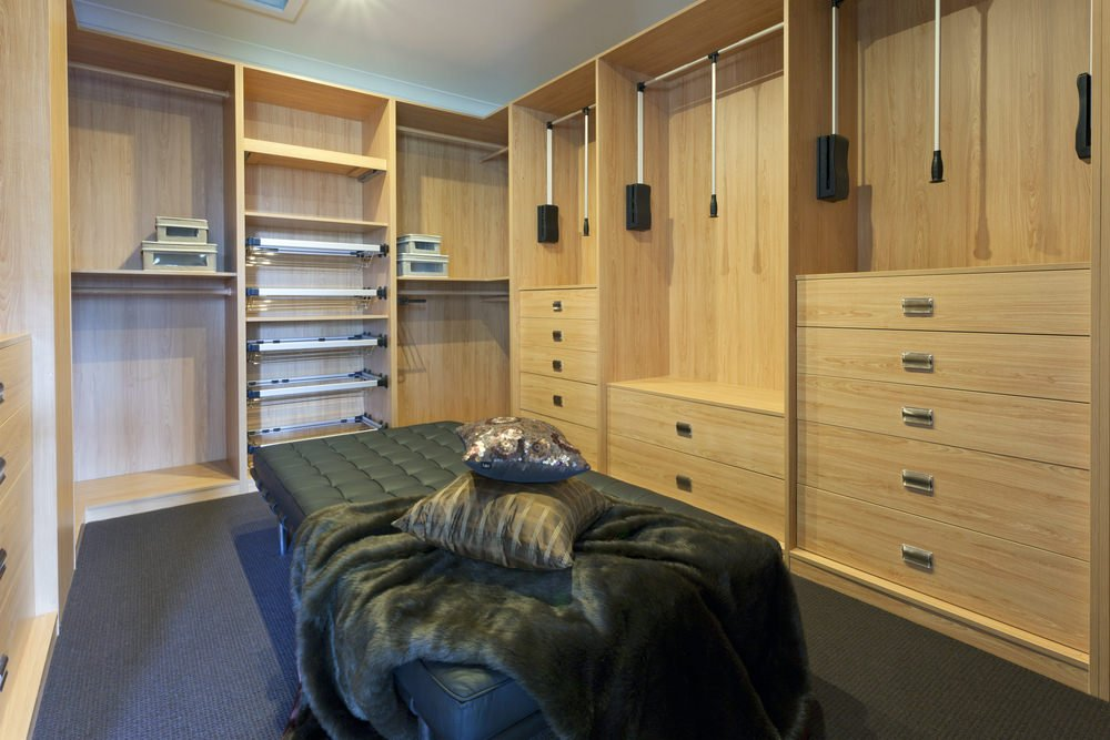 This modern closet boasts walnut finished cabinetry, black carpet and center seat and a skylight ceiling.