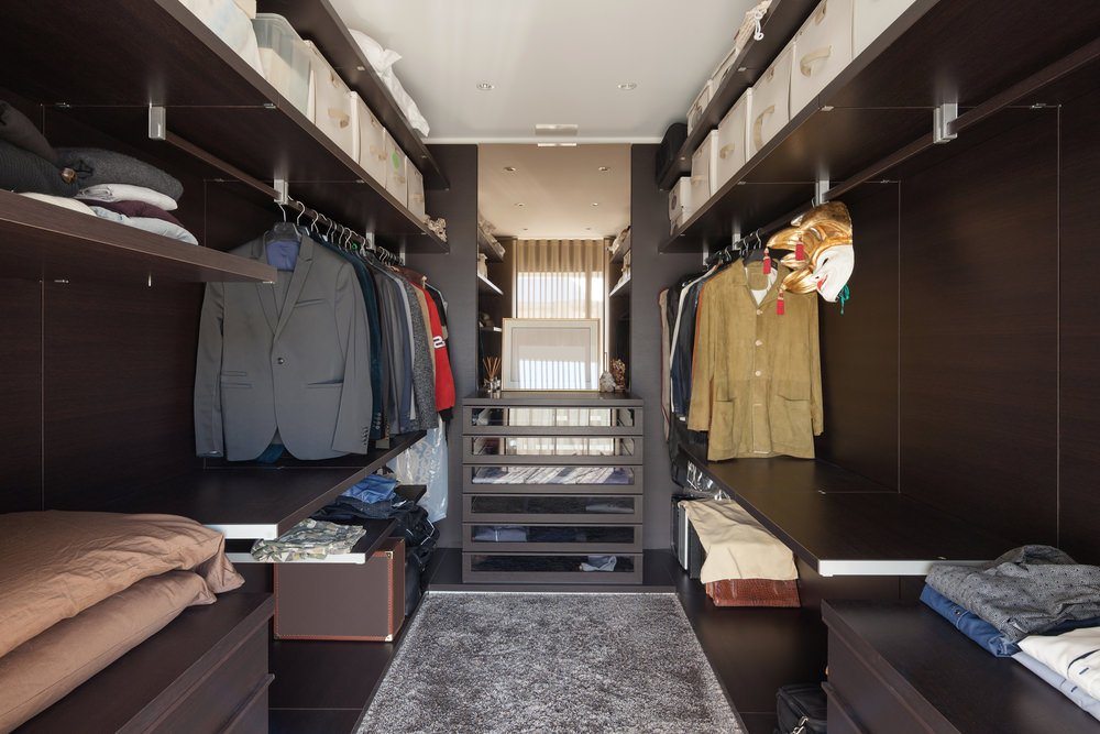 This bedroom closet features a dark brown cabinetry and flooring topped by a gray rug. This room is lighted by a set of recessed lights.