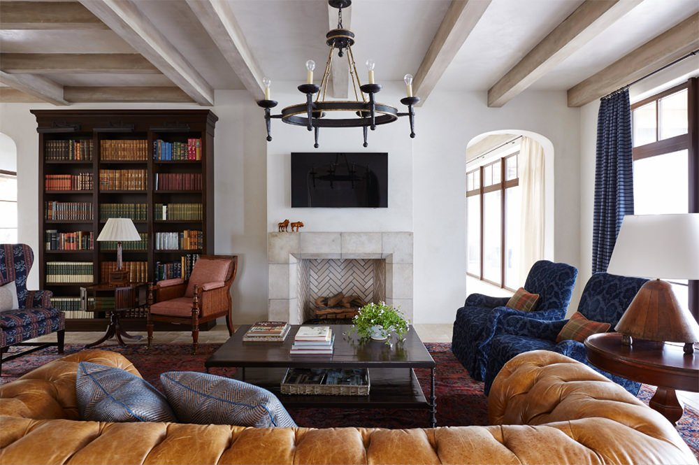 A tufted sofa faces the chevron fireplace and television in this living room with a wooden bookshelf accompanied by mismatched chairs and round table.