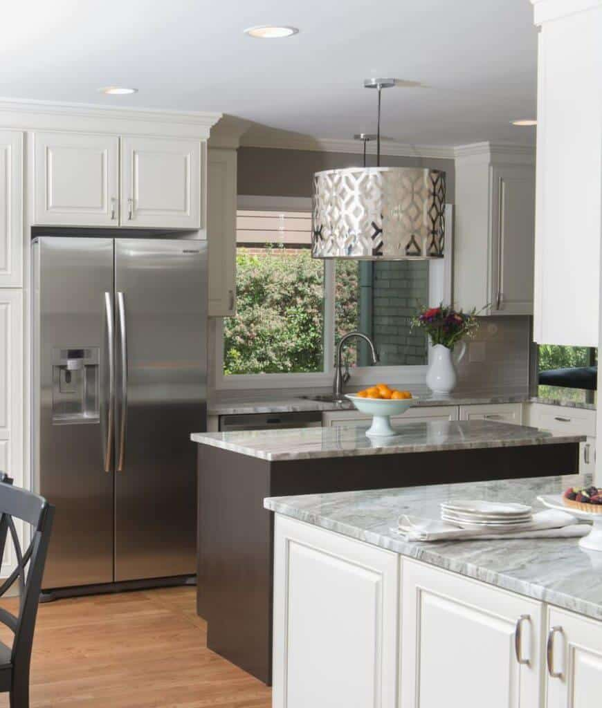A stylish drum pendant illuminates this kitchen featuring white cabinetry and dark wood kitchen island topped with gray marble counter and a white bowl.