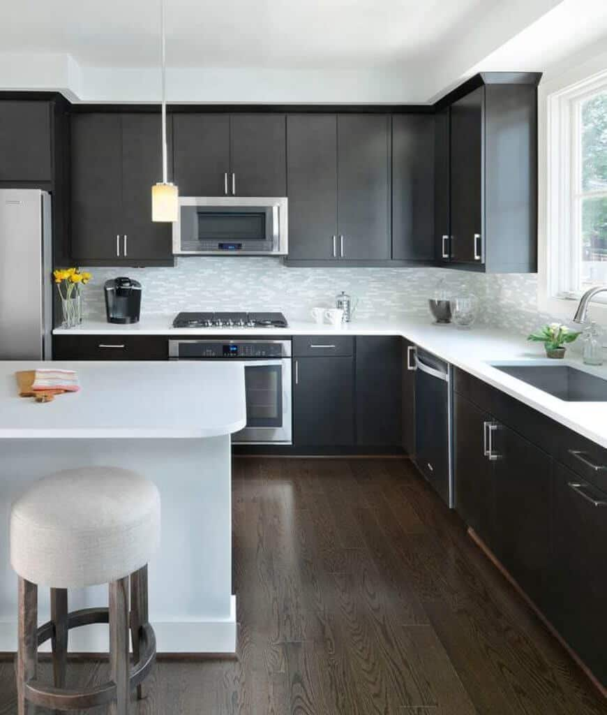 This kitchen offers black cabinetry beautifully contrasted with a white breakfast island on a dark hardwood flooring lighted by a glass pendant.