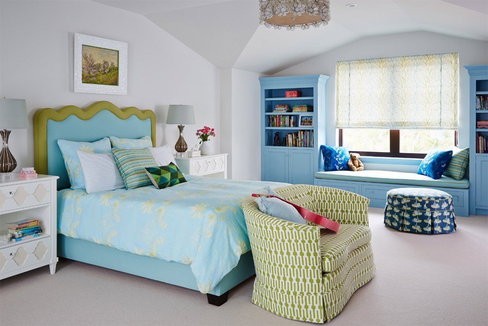 Fabulous guest bedroom offers a charming bed with a green patterned couch on its end along with a window seat nook accented with striped and blue pillows complementing with the skirted ottoman.