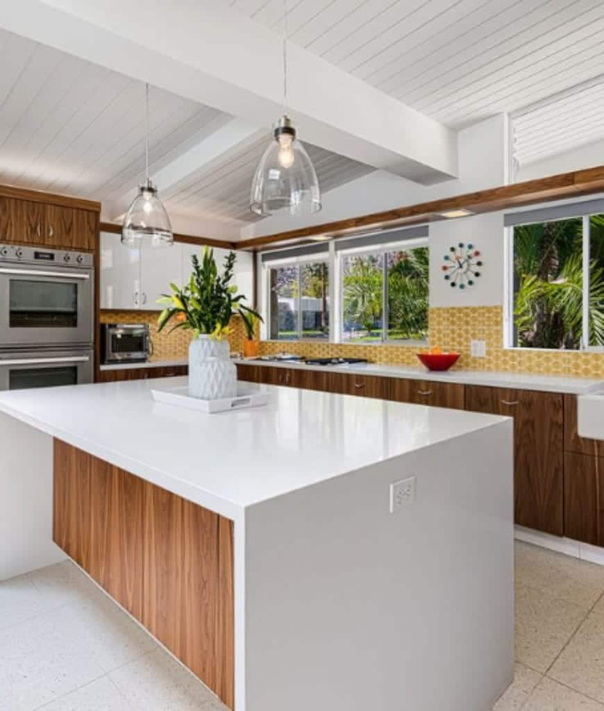 Charming kitchen designed with yellow hex tile backsplash and a multicolored wall clock mounted on the white wall. It has sleek kitchen island lighted by glass pendants that hung from the white beamed ceiling.