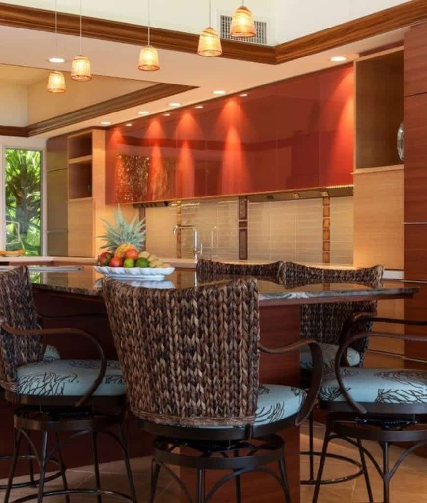 Luxury kitchen with red high gloss cabinetry and a wooden island bar paired with wicker chairs and lighted by warm pendants.