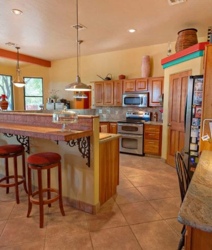 Yellow kitchen showcases a two-tier breakfast island and wooden cabinetry with stainless steel appliances inset. It has chrome pendant lights and a wooden door that leads to the pantry.